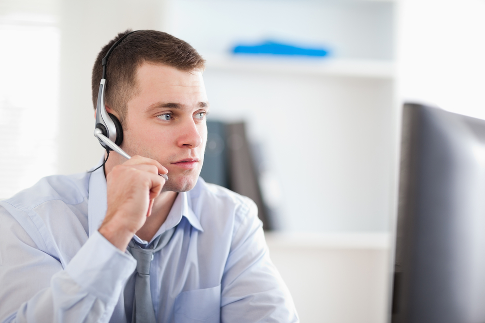 Young call center agent speaking with customer